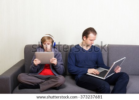 Father and son sitting apart on the couch