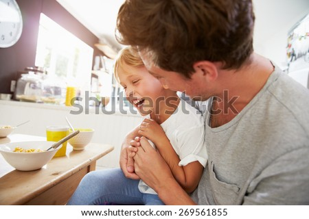 Father And Son Sitting At Breakfast Table Together - stock photo