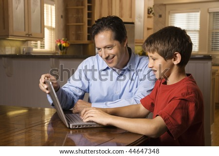 Father and son sitting at dining room table working on wireless laptop computer. - stock photo