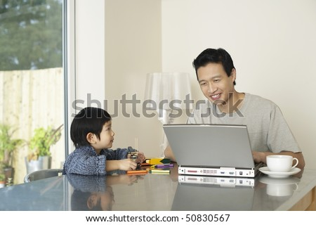 Father and son sitting at kitchen table, Father working on computer