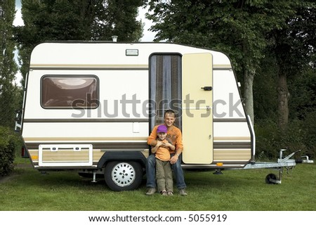 Father and son sitting in front of a caravan - stock photo