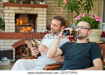 father and son sitting in front of fireplace and drinking beer - stock photo
