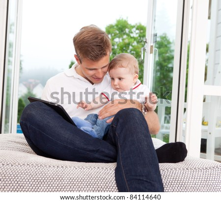 Father and son sitting in front of window using a digital tablet - stock photo