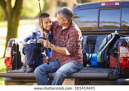 Father And Son Sitting In Pick Up Truck On Camping Holiday - stock photo
