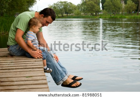 Father and son sitting near a river - stock photo