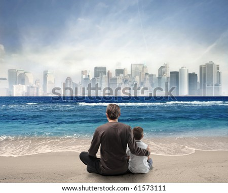 Father and son sitting on a beach looking over a city - stock photo