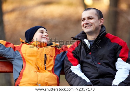 Father and son sitting on a bench and talking - stock photo