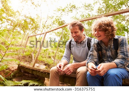 Father and son sitting on a bridge in a forest, close up - stock photo