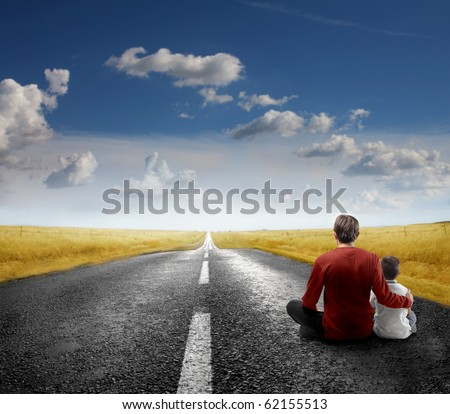 Father and son sitting on a road - stock photo