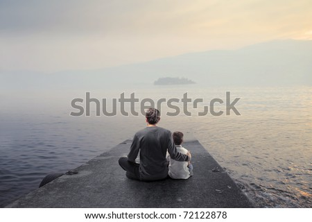 Father and son sitting on a wharf and observing the panorama - stock photo