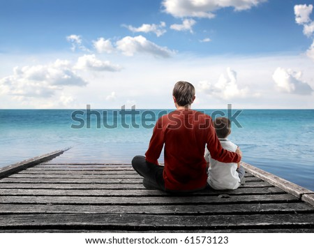 Father and son sitting on a wharf over the sea - stock photo