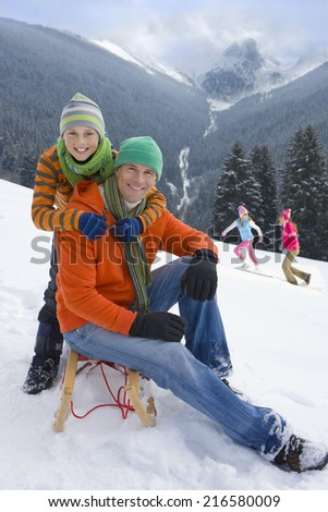 Father and son sitting on sled on ski slope