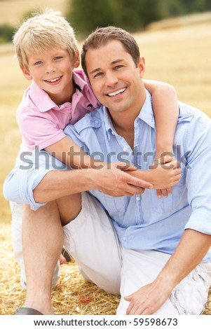 Father And Son Sitting On Straw Bales In Harvested Field - stock photo