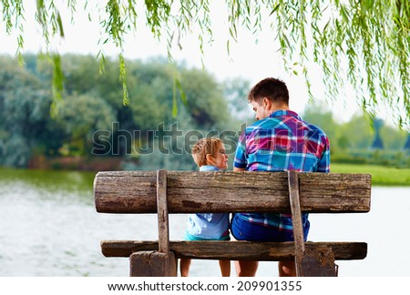 father and son sitting on the bench near the lake - stock photo