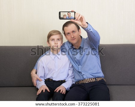 Father and son sitting on the couch and taking selfie photo together