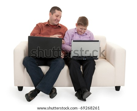 Father and son sitting on the couch with laptops - stock photo