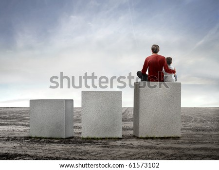 Father and son sitting on the highest of three cubes on a field - stock photo