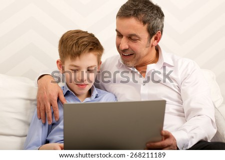 Father and son sitting on the sofa at home. Happy dad embracing boy and watching him working with laptop