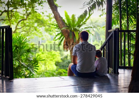 father and son sitting on tree house stairs in tropical forest - stock photo