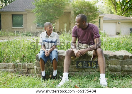 Father and son sitting on wall - stock photo