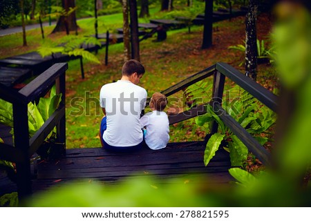 father and son sitting on wooden stairs in rain forest - stock photo