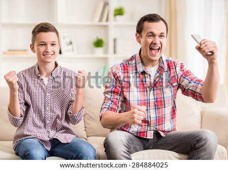 Father and son sitting together at sofa and watching football match. - stock photo