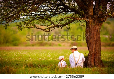father and son sitting under the tree on spring lawn - stock photo