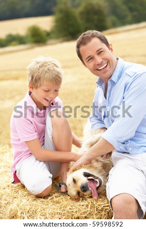 Father And Son Sitting With Dog On Straw Bales In Harvested Field - stock photo