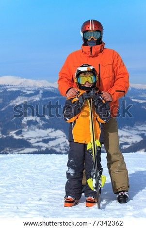 Father and son skiers stand on the top of snow covered mountain. - stock photo