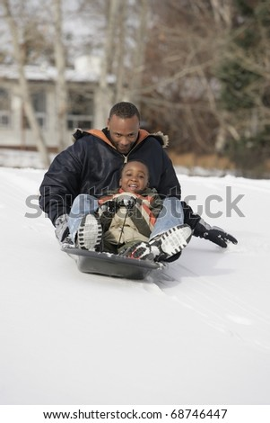 Father And Son Sledding On Snow - stock photo