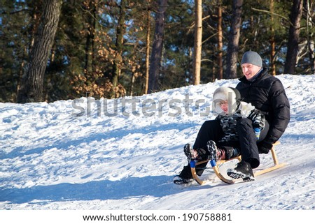 Father and son sliding in snow. - stock photo