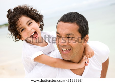 father and son smiling at the beach - stock photo