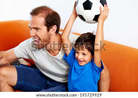 father and son soccer fans cheering with football ball - stock photo