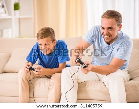 Father and son spend time together, are playing game. - stock photo