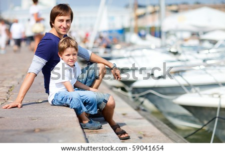 Father and son spending time at marina in city center on summer day - stock photo