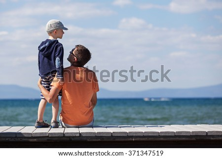 father and son spending time together at the dock at the lake tahoe, california, father's day concept - stock photo