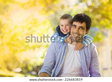 Father and son spending time together in sunny nature, son is hugging father - stock photo