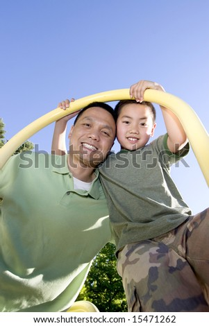 Father and son stand beneath fireman's pole on jungle gym. Father and son are looking down and smiling at the camera. Vertically framed photo. - stock photo