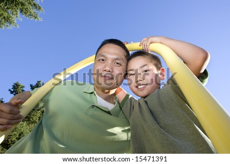 Father and son stand beneath fireman's pole on jungle gym. Father and son are looking down and smiling at the camera. Horizontally framed photo. - stock photo