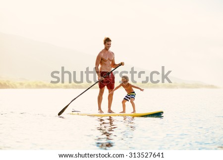 Father and Son Stand Up Paddling at Sunrise - stock photo