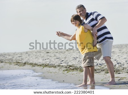 Father and Son Standing by the Ocean - stock photo