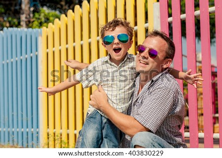 Father and son standing near the multicolored fence at the day time. Concept of friendly family. - stock photo