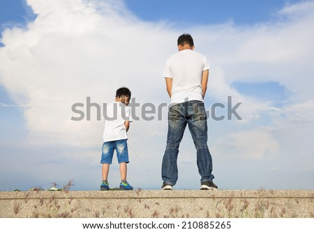 father and son standing on a stone platform and pee together  - stock photo