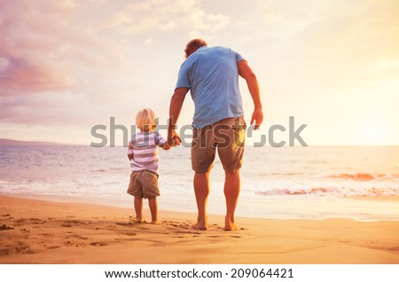 Father and son standing on the sea shore holding hands at sunset - stock photo