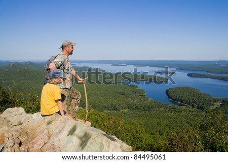Father and son standing on top of the Pinnacle mountain and look at the magnificent view - stock photo
