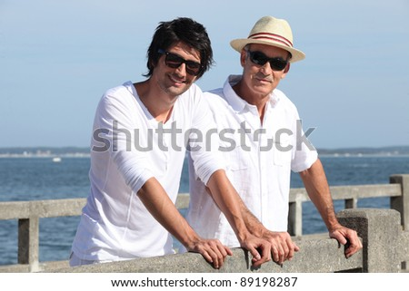 Father and son stood by waterfront - stock photo
