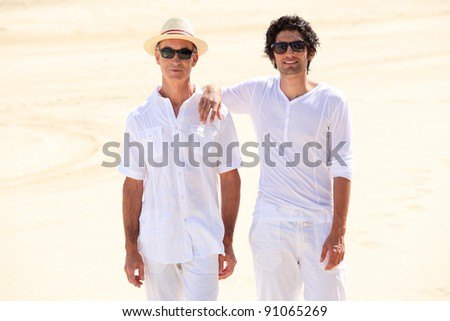 Father and son stood on beach - stock photo
