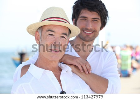 Father and son stood on pier - stock photo