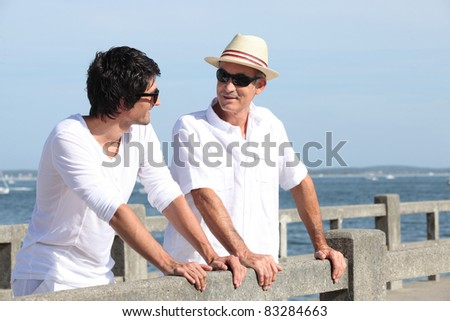 Father and son stood on promenade - stock photo