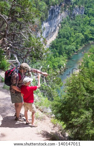 Father and son stood on the big bluff. Adult shows the child view of the Buffalo River in Arkansas - stock photo